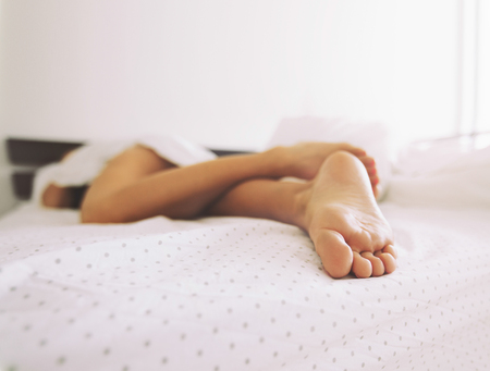 Feet of a woman sleeping in bed at home. Legs of a female lying on bed - Indoors photo