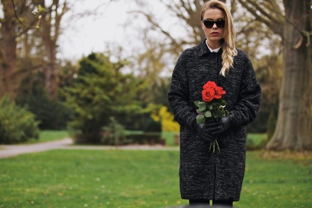 widow: Portrait of sad young woman in black dress at cemetery holding fresh roses. Female at graveyard with flowers. Stock Photo