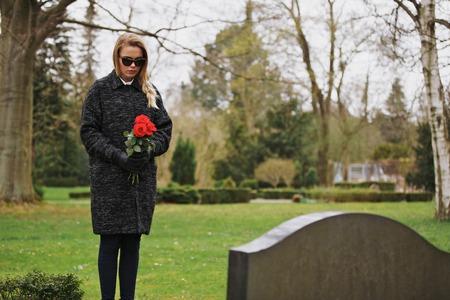 사망 한 가족의 묘비에 서있는 젊은 여자. 묘지 슬픔 꽃을 들고의 여성.