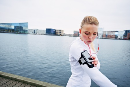 Beautiful young woman training outdoors while using a smartphone to monitor her progress. Caucasian female runner. photo
