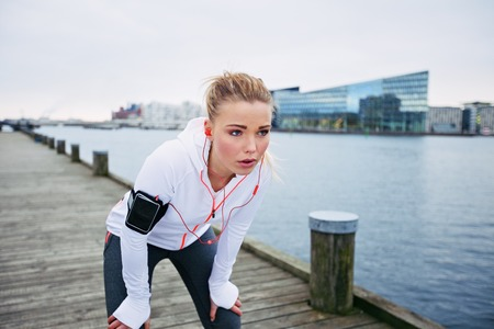 Young female runner stopping for a rest while out on a run along river. Fitness woman taking a break from training session outdoors.