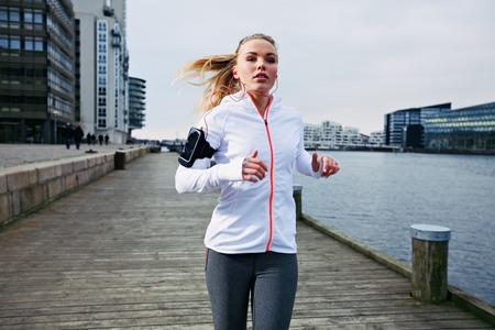 Fit young woman running on the boardwalk along river. Caucasian female athlete training outdoors by the waterfront. photo
