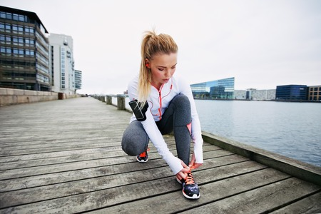 tracksuit: Young woman tying her shoelaces before a run along waterfront. Female runner preparing foe sprint. Fit female athlete on boardwalk along river.