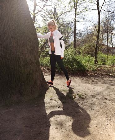 hamstrings: Young woman stretching her hamstrings by a tree before a jog on a forest trail. Caucasian female model exercising in park.