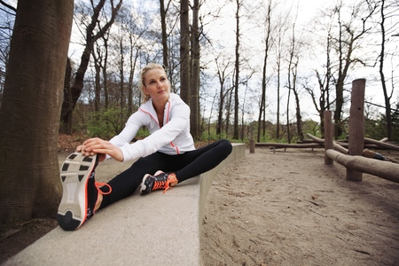 Woman doing stretching exercise in park. Caucasian female model exercising in nature. photo