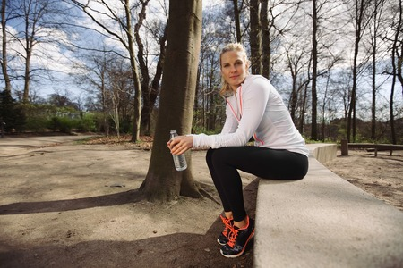 taking a break: Female runner taking a break from running in forest. Beautiful young female athlete sitting with a water bottle looking at camera. Stock Photo