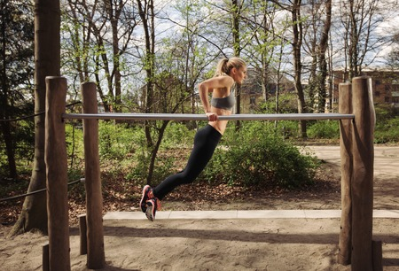 physically: Strong and physically fit young woman doing triceps dips on parallel bars at park. Caucasian fitness female exercising outdoors. Stock Photo