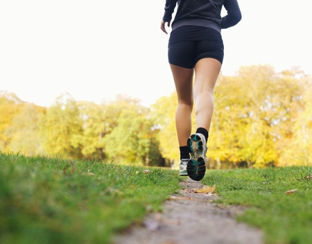 Rear view of woman athlete jogging in park. Female fitness model running outdoors photo
