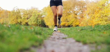 Low section image of young womans legs running in park. Female athlete jogging in a park on a summer day. photo