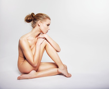 nude woman sitting: Gorgeous young nude woman sitting on the floor. Caucasian female model covering her body with her leg looking away at copy space on grey background