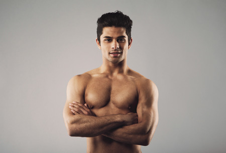 Portrait of a bare-chested muscular man standing with his arms crossed. Fit and masculine young hispanic man shirtless on grey . photo