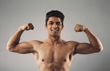 show off: Portrait of hispanic young muscular man flexing his biceps isolated on grey . Happy masculine man pulling his biceps to show off.
