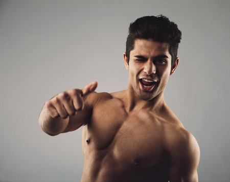 Portrait of a happy young man with muscular physique winking and giving a thumbs up sign. Shirtless young hispanic man on grey . Focus on hand.