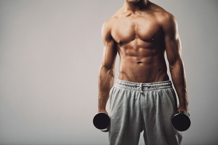man working out: Studio shot of a male model in sweatpants holding dumbbells in both hands on grey with copy space. Shirtless muscular man working out. Health and fitness theme.