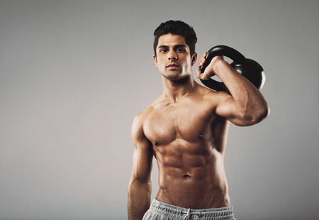 Handsome muscular man holding kettle bell with copy space. Hispanic male athlete working out with kettlebell on grey . Crossfit workout theme.