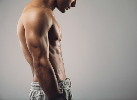 Cropped image of muscular young man torso on grey with copy space. Stock Photo