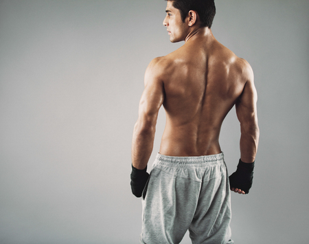 shirtless man: Rear view of muscular young male boxer standing looking away. Fit young man wearing boxing gloves on grey . Stock Photo