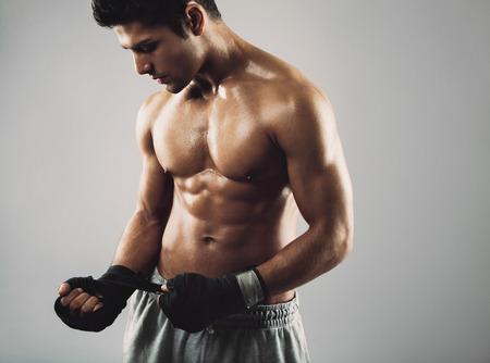 pelea: Boxeador de sexo masculino joven que envuelve las manos en cinta de boxeo antes de una pelea. Modelo de fitness masculino joven hispano.