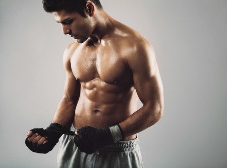 combative: Young male boxer wrapping his hands in boxing tape before a fight. Hispanic young male fitness model.