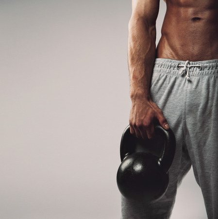 Close up image of young mans hand holding kettle bell. Cross fit workout concept with copyspace on grey . photo
