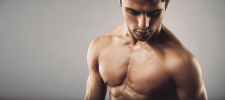 Portrait of fit masculine shirtless man  looking down. Wide panoramic crop with copy space. Workout and fitness theme. Stock Photo