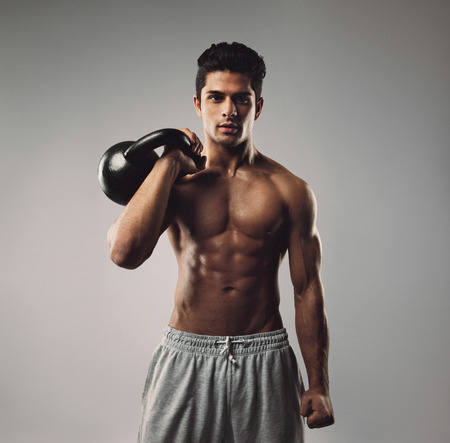 Portrait of strong young man working out with kettle bell. Young muscular guy with cross fit equipment on grey . Stock Photo