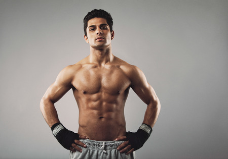 Portrait of muscular man standing with his hands on hips looking at camera with an attitude. Strong young man wearing sports gloves posing confidently. Stock Photo