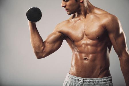 Bebouwd beeld van jonge gespierde man doen zware halter oefening voor biceps. Man uit te werken met halters op grijs. Fitness en training concept.