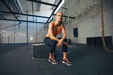 descansando: Joven mujer sentada en una caja en el gimnasio de crossfit mirando lejos. Ajustar joven atleta femenina caucásica en el gimnasio. Foto de archivo