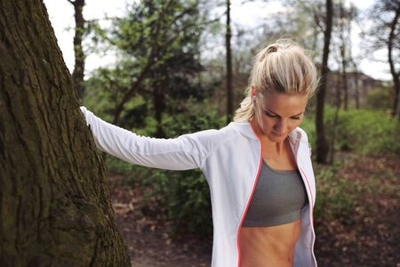female athlete: Beautiful young woman resting by a tree after jogging in a park. Fit female athlete taking a break after running.