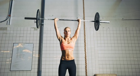 snatch: Muscular young female athlete doing weightlifting at crossfit gym. Fit young woman model lifting heavy weights at gym. Stock Photo