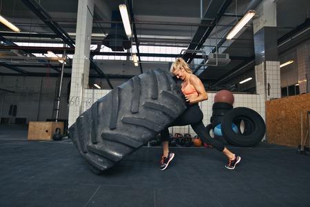 Atleta femenina apta que se resuelve con una enorme llanta, girar y mover de un tirón en el gimnasio. Mujer Crossfit ejercicio con grandes neumáticos.
