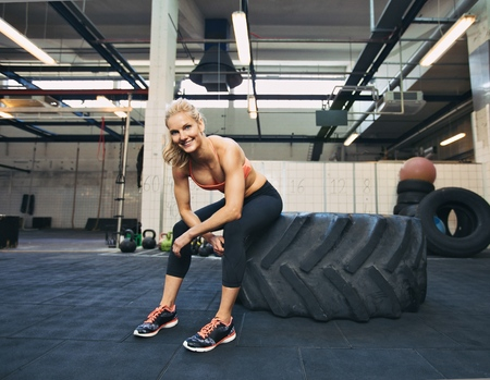 Woman sitting on tire and smiling at camera at gym. Crossfit female athlete taking rest after working out. photo