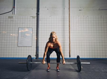Sterke jonge vrouw tillen van zware gewichten op gymnasium. Fitness vrouw doen CrossFit training.