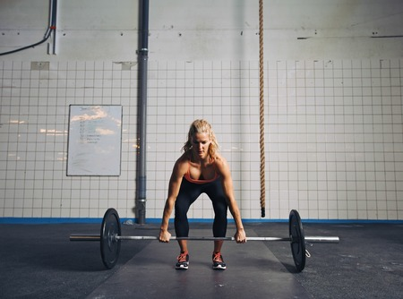 snatch: Strong young woman lifting heavy weights at gym. Fitness female doing crossfit workout.