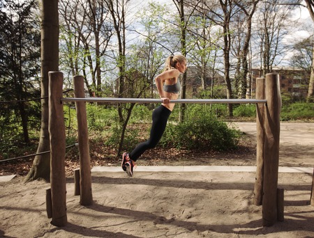 Side view of muscular young woman doing triceps dips on parallel bars at park. Caucasian female fitness model exercising outdoors.