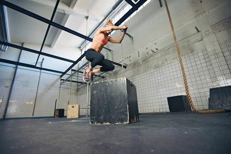Nízký úhel pohledu na mladé ženy sportovec krabice skákání na CrossFit tělocvičně. Fit žena vykonává box skoky v tělocvičně.