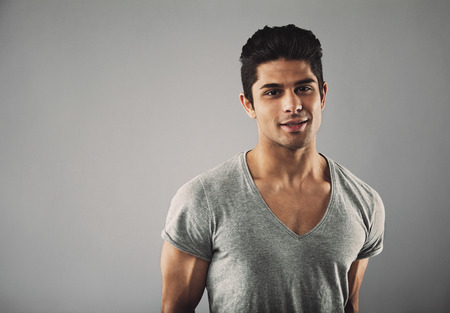 Portrait of handsome young hispanic male fashion model posing against grey background with copy space. Banco de Imagens