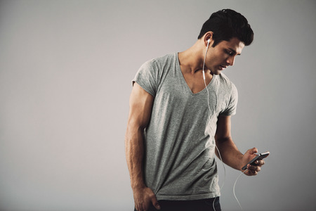 Young hispanic man with cell phone and earphones listening to music on grey background with copy space. Enjoying listening music on smartphone. photo