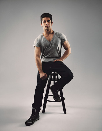bar stool: Full length portrait of handsome young man sitting on bar stool. Young hispanic male model over grey background. Stock Photo