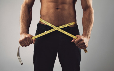 man isolated: Fitness man measuring his body. Cropped and mid-section image of young man measuring his waist with tape measure against grey background. Health and fitness concept.