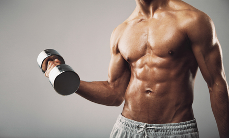 bare chest: Torso shot of a young man with bare chest lifting dumbbells. Fit young man exercising with dumbbells on grey background. Cropped image of sweaty bodybuilder.