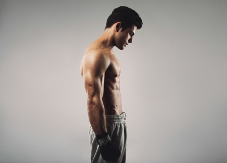 Side view of fit young man wearing boxing gloves looking down on grey background photo