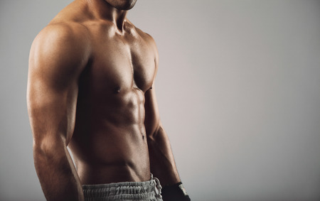 grey background: Close up portrait of shirtless young man standing on grey background. Man with muscular body. Health and fitness concept with copyspace for your text.