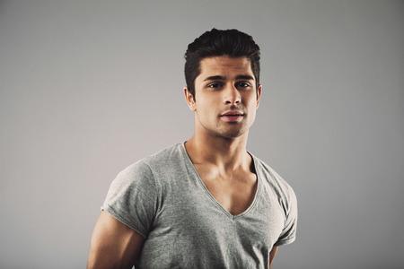 male fashion: Hispanic male fashion model posing against grey background.
