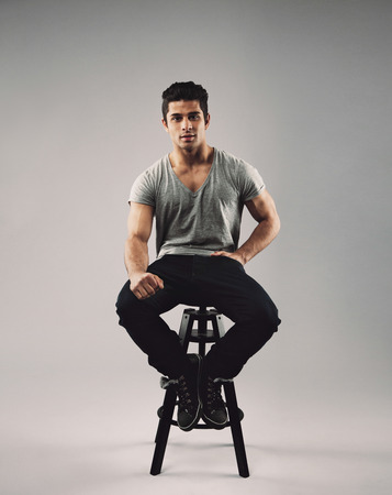 stool: Portrait of smart young man sitting on stool