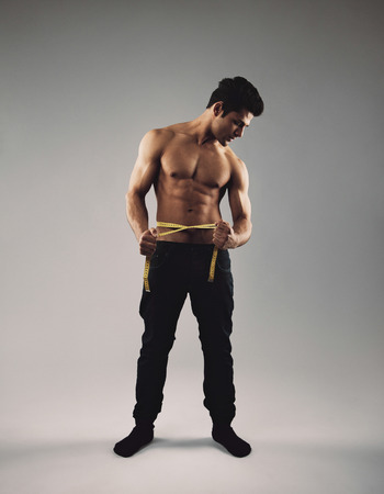 Full length image of fit young man with tape measure around his waist measuring his body