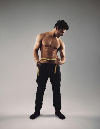 Imagen de la longitud completa del hombre joven del ajuste con la cinta métrica alrededor de su cintura que mide su cuerpo Foto de archivo - 29614853