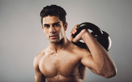 Portrait of hispanic fitness male model holding kettle bell on grey background. Shirtless young doing crossfit work out in studio. photo