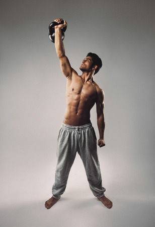 Handsome and athletic young man lifting a kettlebell with one hand photo